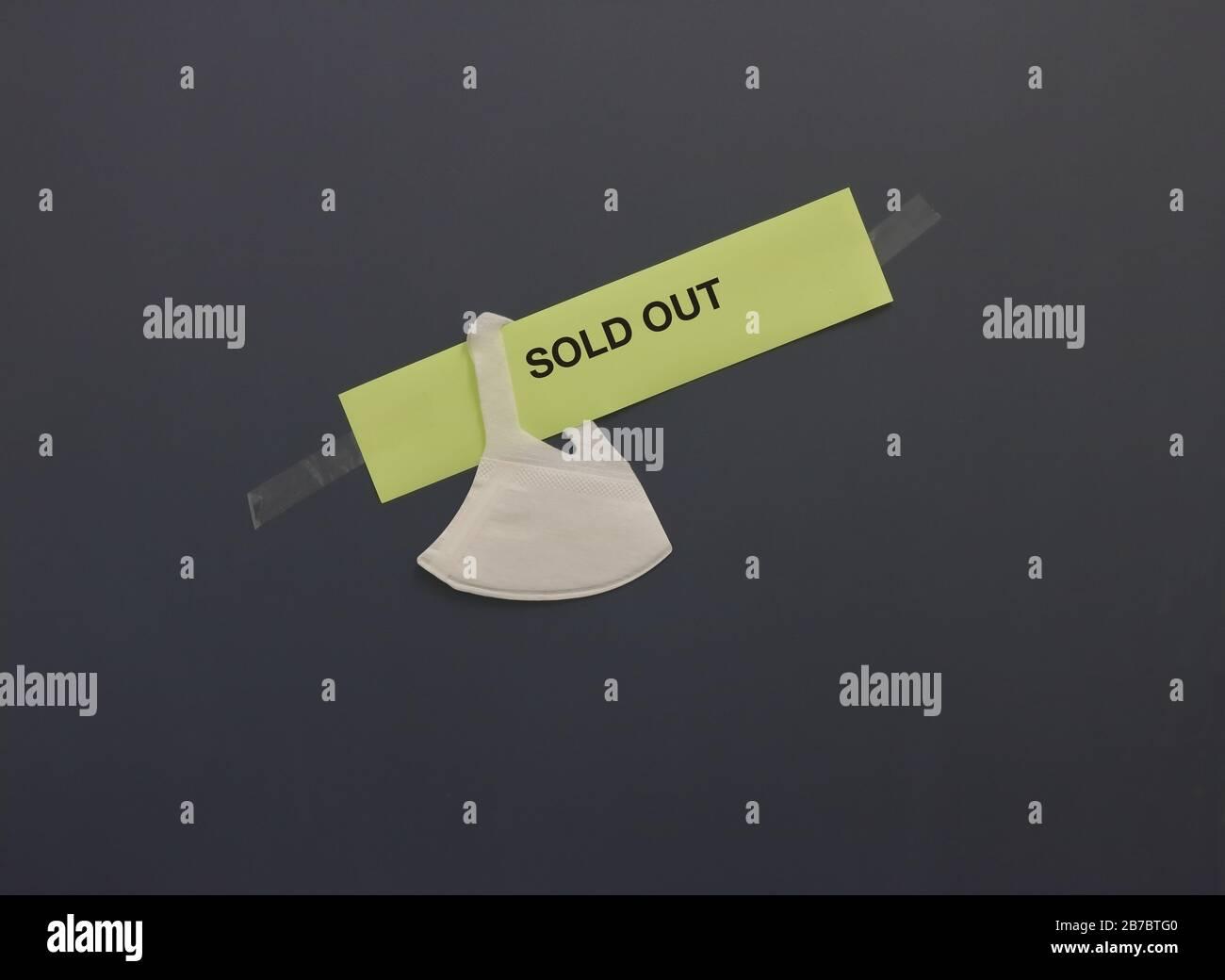 Maschera chirurgica appesa sul cartello di carta con le parole ESAURITE attaccate sul vetro colorato di un negozio. Persone che schermano maschera facciale come risultato di covid19 focolaio Foto Stock