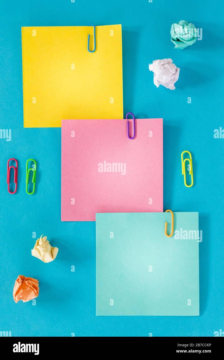 Carte colorate con spazio per un'iscrizione, ufficio o concetto di business, punti metallici, palle di carta sbriciolate. Foto Stock