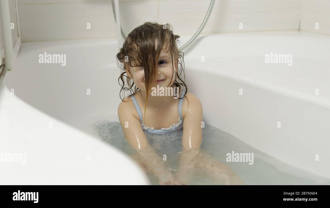 Attraente ragazza di quattro anni prende un bagno con schiuma bagno in costume da bagno. Lava la testa. Capelli bagnati. Igiene per il bambino biondo carino. Ragazza carina sorridente. Bambino piccolo, 4-5 anni bionda ragazza in bagno Foto Stock