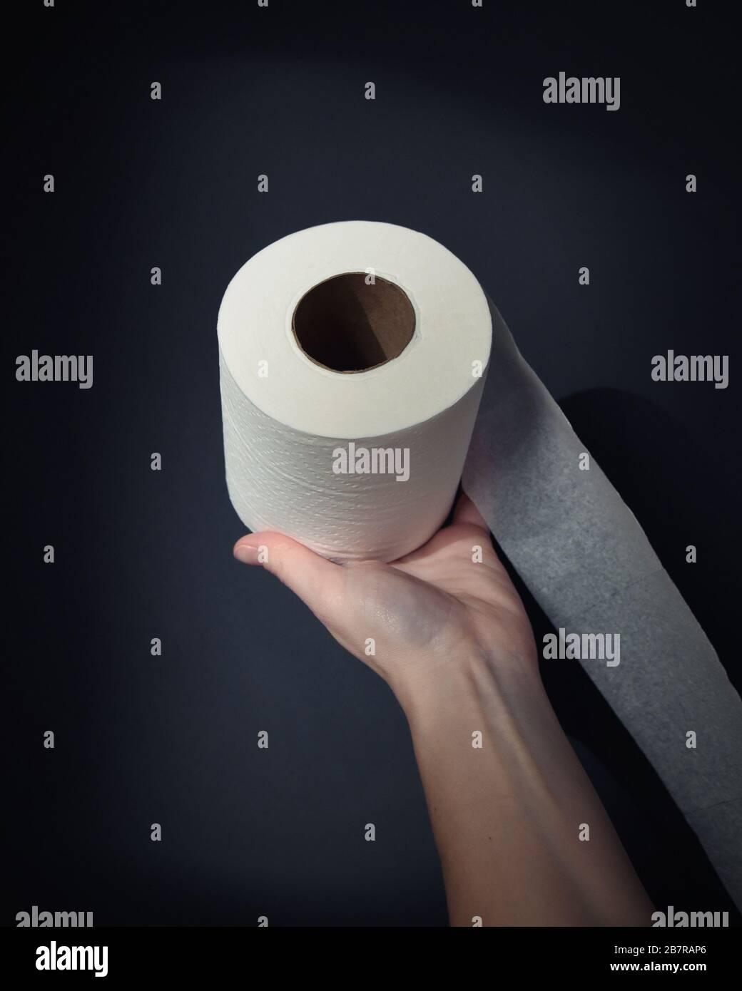 Una mano sta tenendo un rotolo di carta igienica con un riflettore sull'oggetto per una mancanza di offerta e di domanda di carta igienica sulla pandemia del virus della corona. Foto Stock