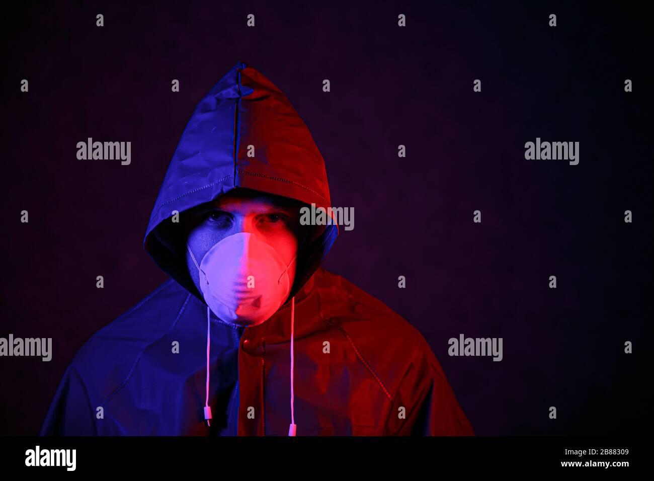 Coronavirus. Un uomo in maschera e tuta di protezione chimica in luce rossa e blu. Lotta contro il virus Foto Stock