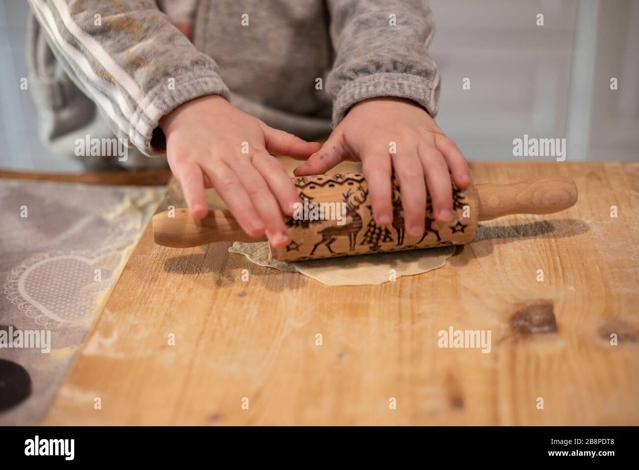 Le mani della ragazza del bambino, nella cucina bianca, appiattendo l'impasto della pizza con un piccolo perno di rotolamento su una tavola di legno. Idea dell'attività di blocco. Foto Stock