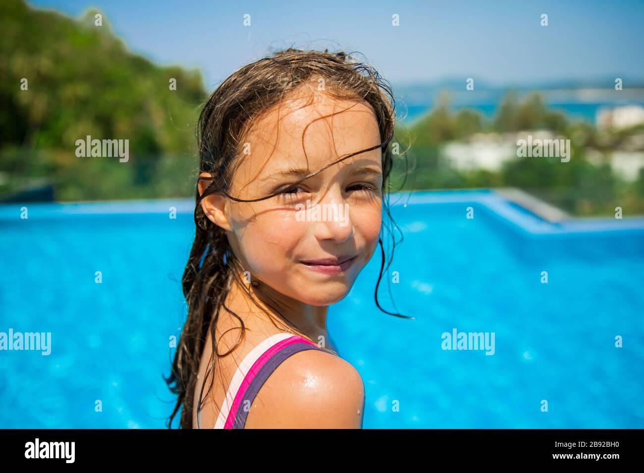 Ritratto di bambina felice in piscina guardando nella macchina fotografica. Buona vacanza estiva. Foto Stock