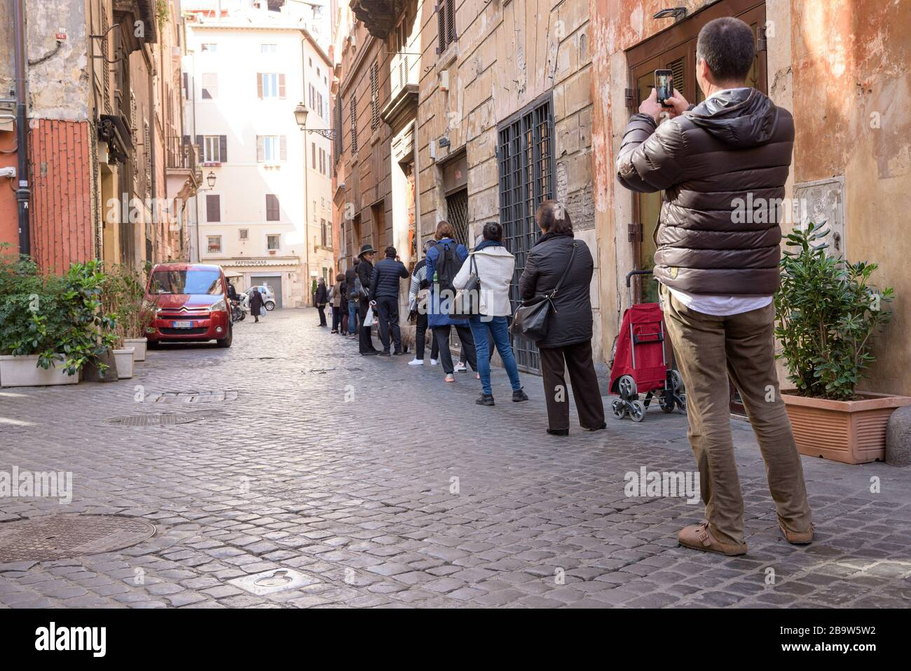 ROMA, ITALIA - 12 marzo 2020: I clienti si allineano al di fuori di un supermercato locale nel centro di Roma. Solo poche persone possono entrare alla volta, e scal Foto Stock