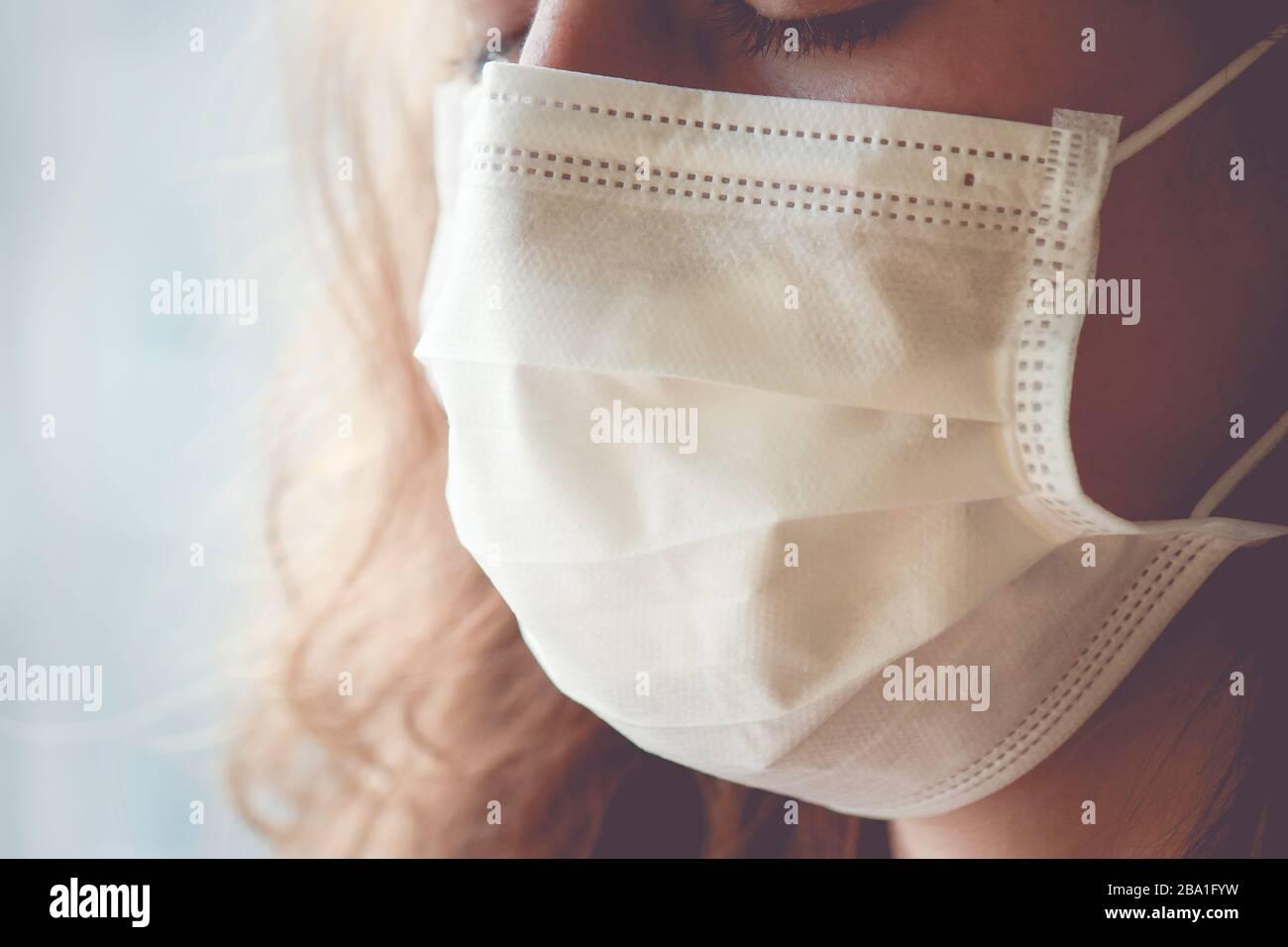Particolare della donna caucasica che indossa una maschera medica bianca per il viso. La donna sta piangendo, gli occhi chiusi. Mettere a fuoco sulla parte anteriore del viso, sfondo sfocato. Coronavirus, quarantena COVID-19. Concetto di infermiere. Foto Stock