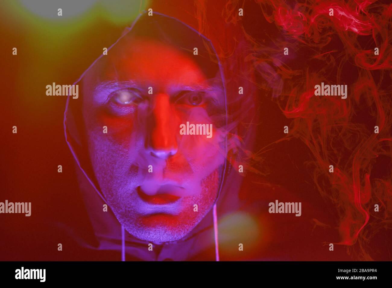 Un uomo in maschera e tuta di protezione chimica in luce rossa e blu. Lotta contro il virus Foto Stock