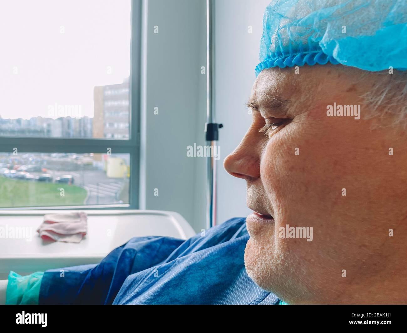 Primo piano del volto maschile senior in sedia medica all'interno del moderno ospedale in Francia a riposo dopo infezione virus coronavirus visione ottimistica Foto Stock