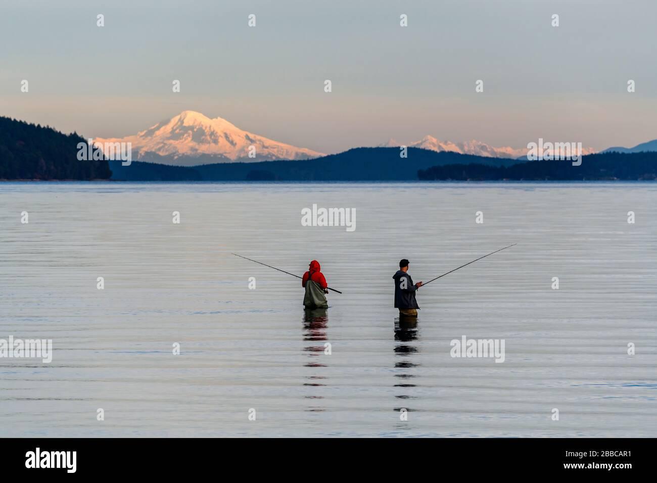 Due uomini di pesca oceanica a Cherry Point Beach vicino Cowichan Bay, British Columbia. Mt. Baker nello Stato di Washington è sullo sfondo. Foto Stock