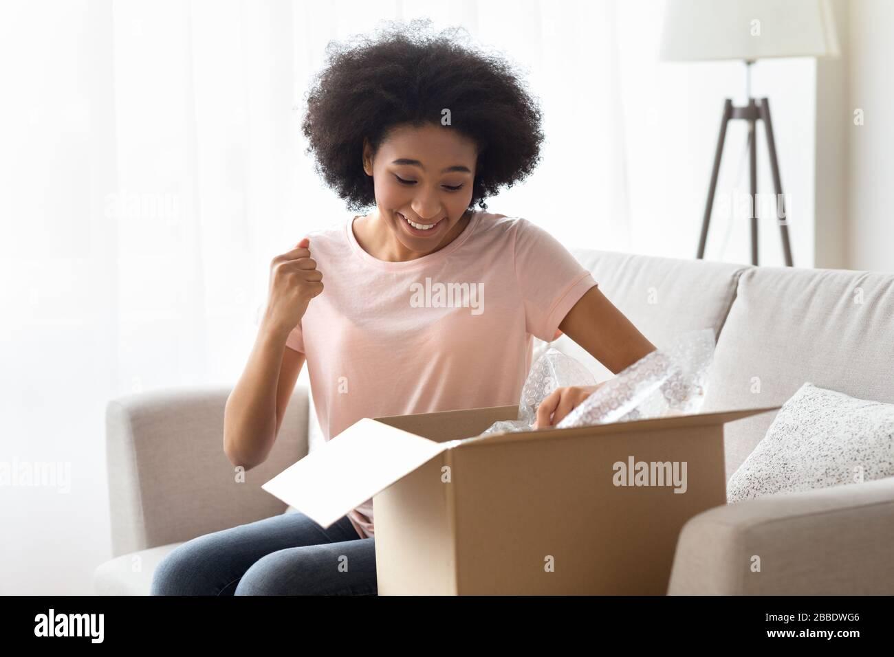 La donna afroamericana apre una scatola e gioisce Foto Stock