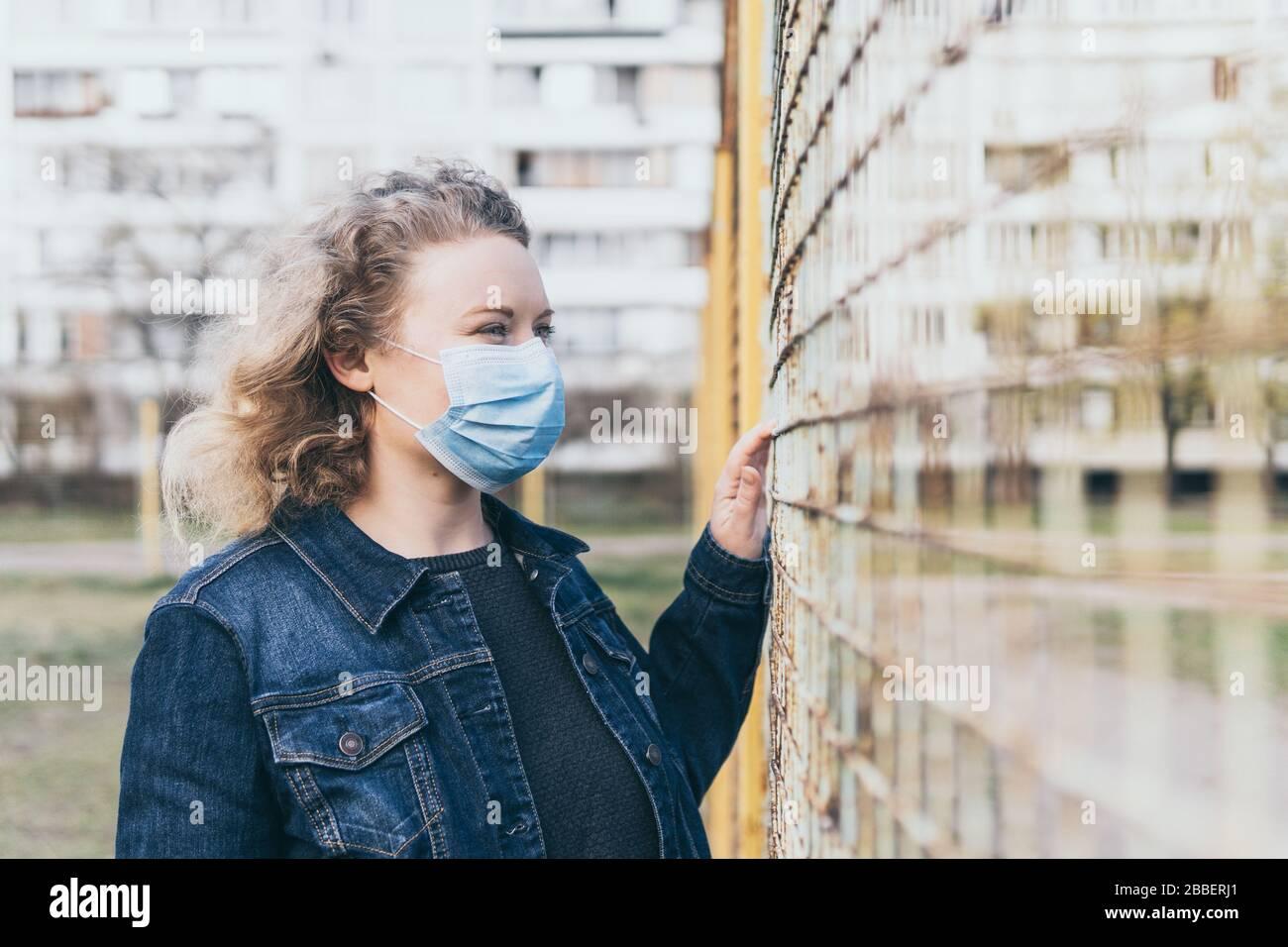 L'Europa orientale ha interessato la donna che indossa la maschera medica all'aperto, in piedi vicino alla recinzione di maglia con l'edificio residenziale sullo sfondo. Virus corona Foto Stock