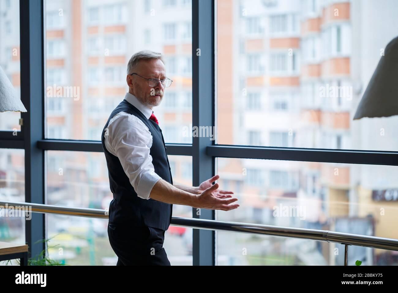 Sorridendo felice amministratore delegato pensa al suo successo di carriera sviluppo, mentre si trova in ufficio vicino allo sfondo di una finestra con copia sp Foto Stock