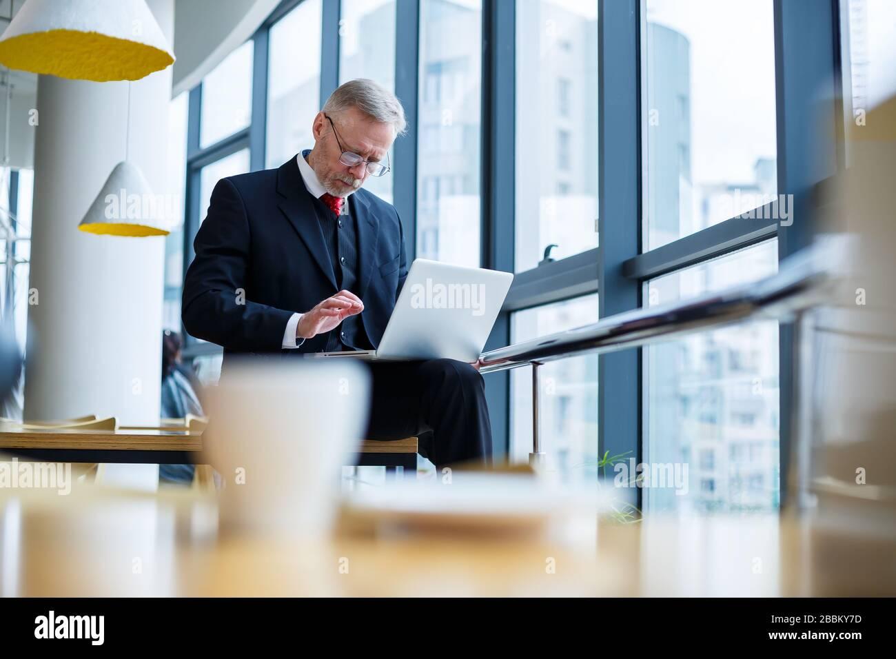Sorridendo felice direttore di gestione pensa al suo successo di carriera sviluppo, mentre in piedi con un notebook nel suo ufficio vicino allo sfondo di una vittoria Foto Stock