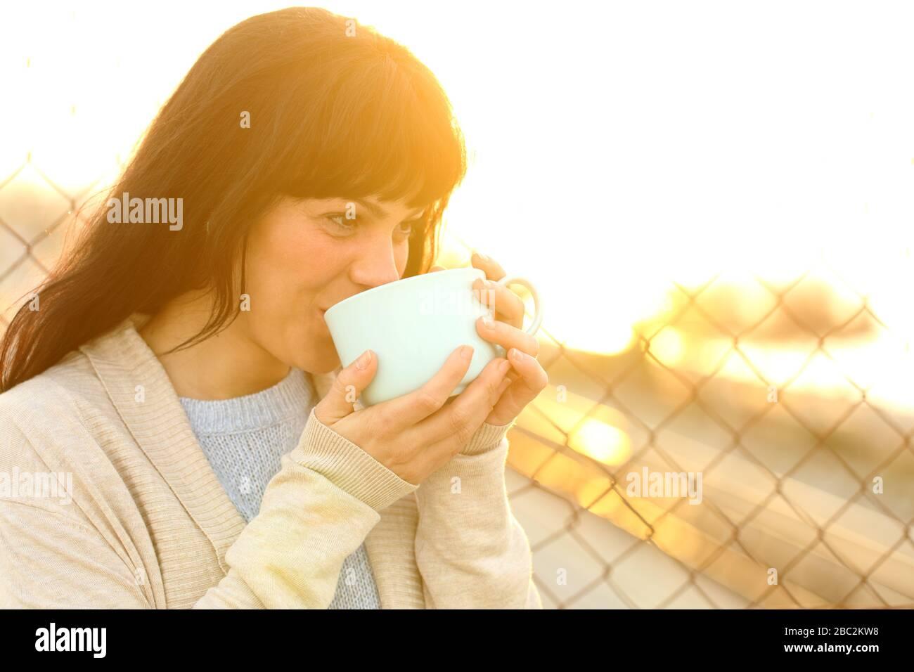 Buona donna adulta bevendo caffè al tramonto in strada Foto Stock