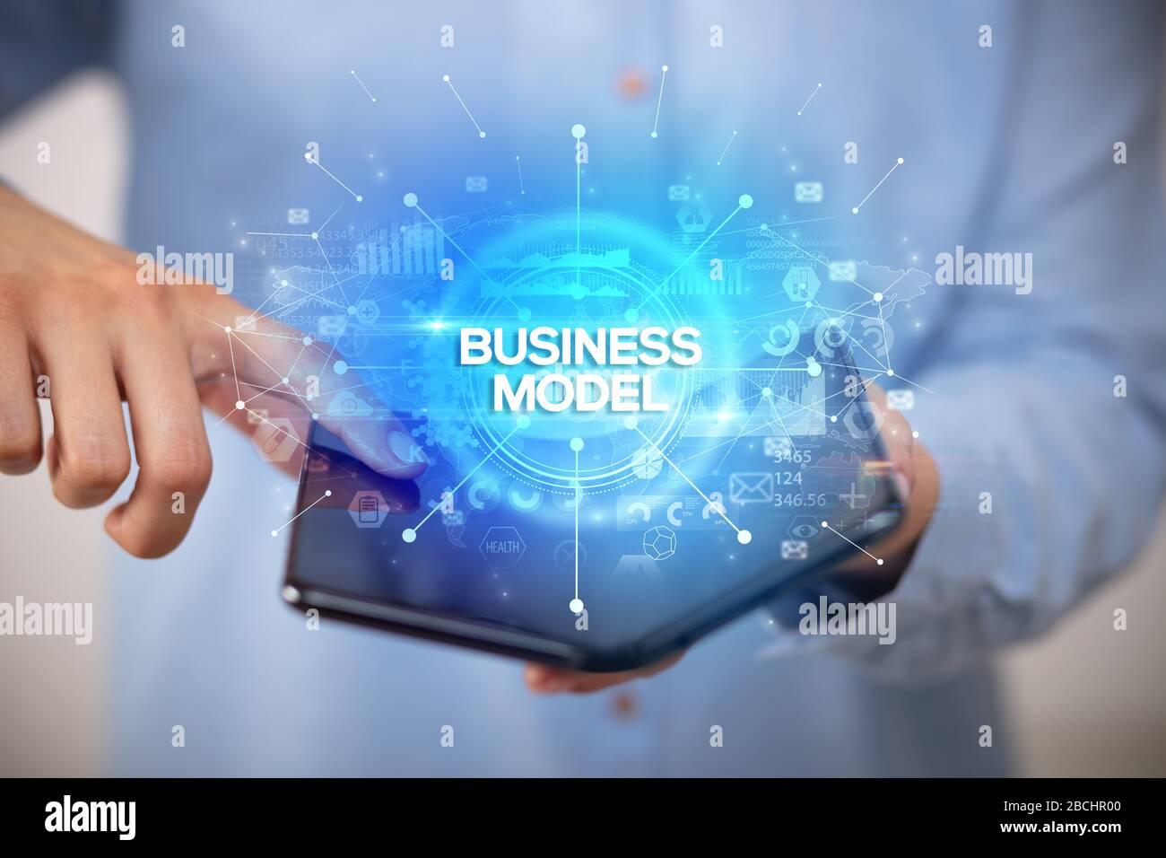 Imprenditore tenendo un smartphone pieghevole con il modello di business iscrizione, nuovo concetto di business Foto Stock