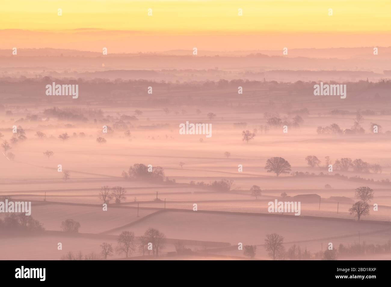 Dawn sopra la nebbia avvolta campagna dei livelli del Somerset in inverno, Glastonbury, Somerset, Inghilterra, Regno Unito, Europa Foto Stock