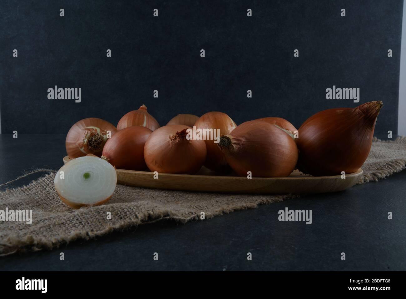 Un gruppo di cipolle su sfondo scuro Foto Stock