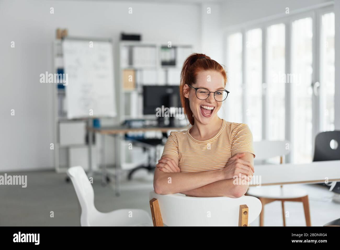 Giovane allegra donna che si annida alla macchina fotografica con un'espressione saucy mentre si siede distendendosi su una sedia in un ufficio chiave Foto Stock