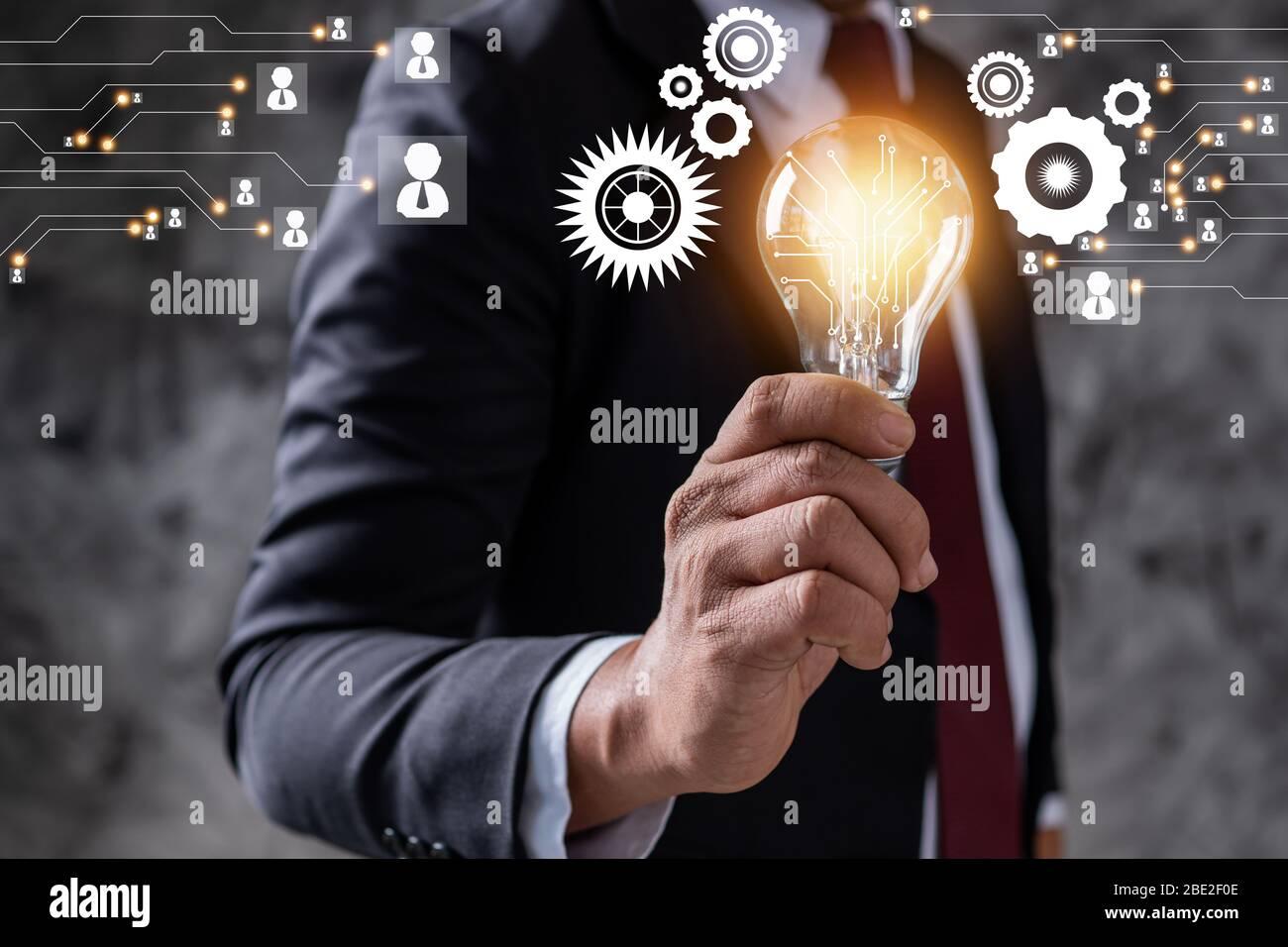Innovazione e idea di azienda leader professionale che detiene lampadina di illuminazione, gestione di pensiero e potenza del concetto tecnologico Foto Stock