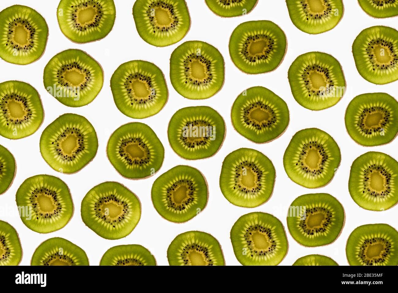 una bella immagine di un interessante modello di fette di kiwi su uno sfondo bianco brillante, flatlay Foto Stock