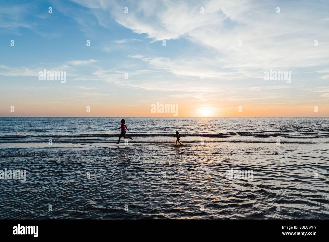 donna e bambino corrono nelle acque poco profonde di una spiaggia della florida al tramonto Foto Stock