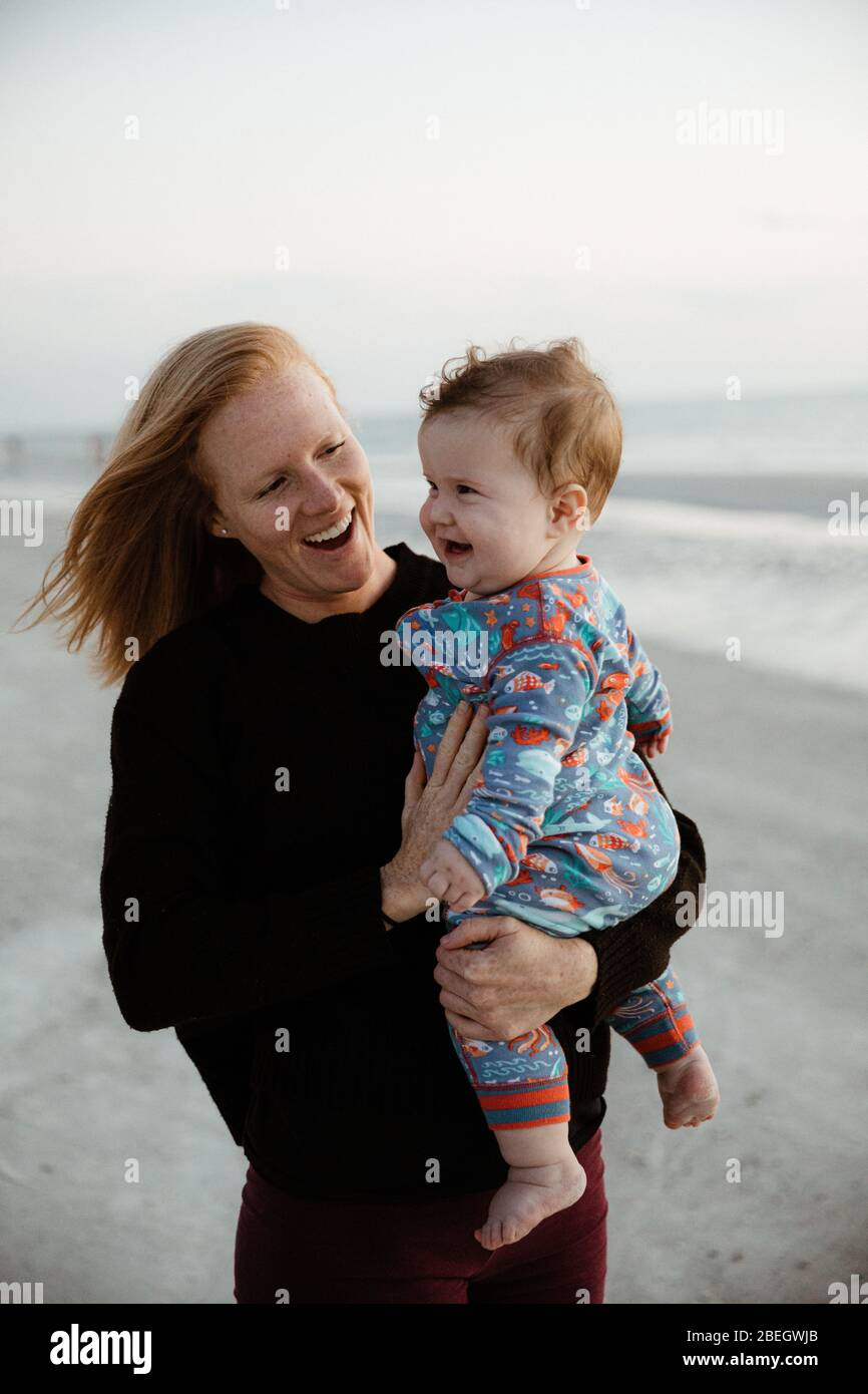 giovane madre e bambino sano ragazzo cotto sorridere durante la passeggiata sulla spiaggia Foto Stock