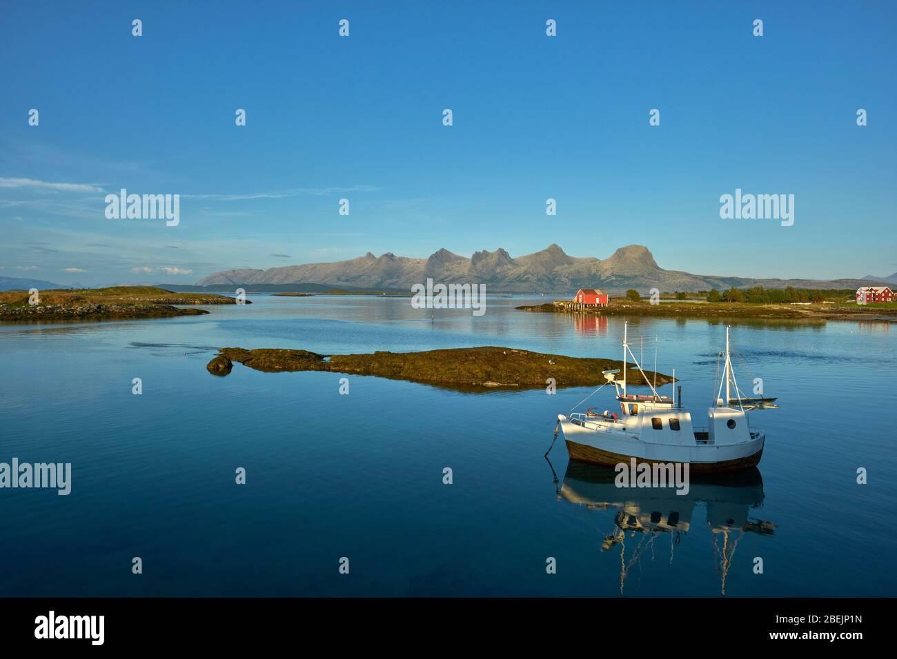 Una barca da pesca solista ormeggiata nel mare ancora estivo di South Heroy e Alsta e la catena montuosa delle sette Sorelle in Helgeland Nordland Norvegia Foto Stock