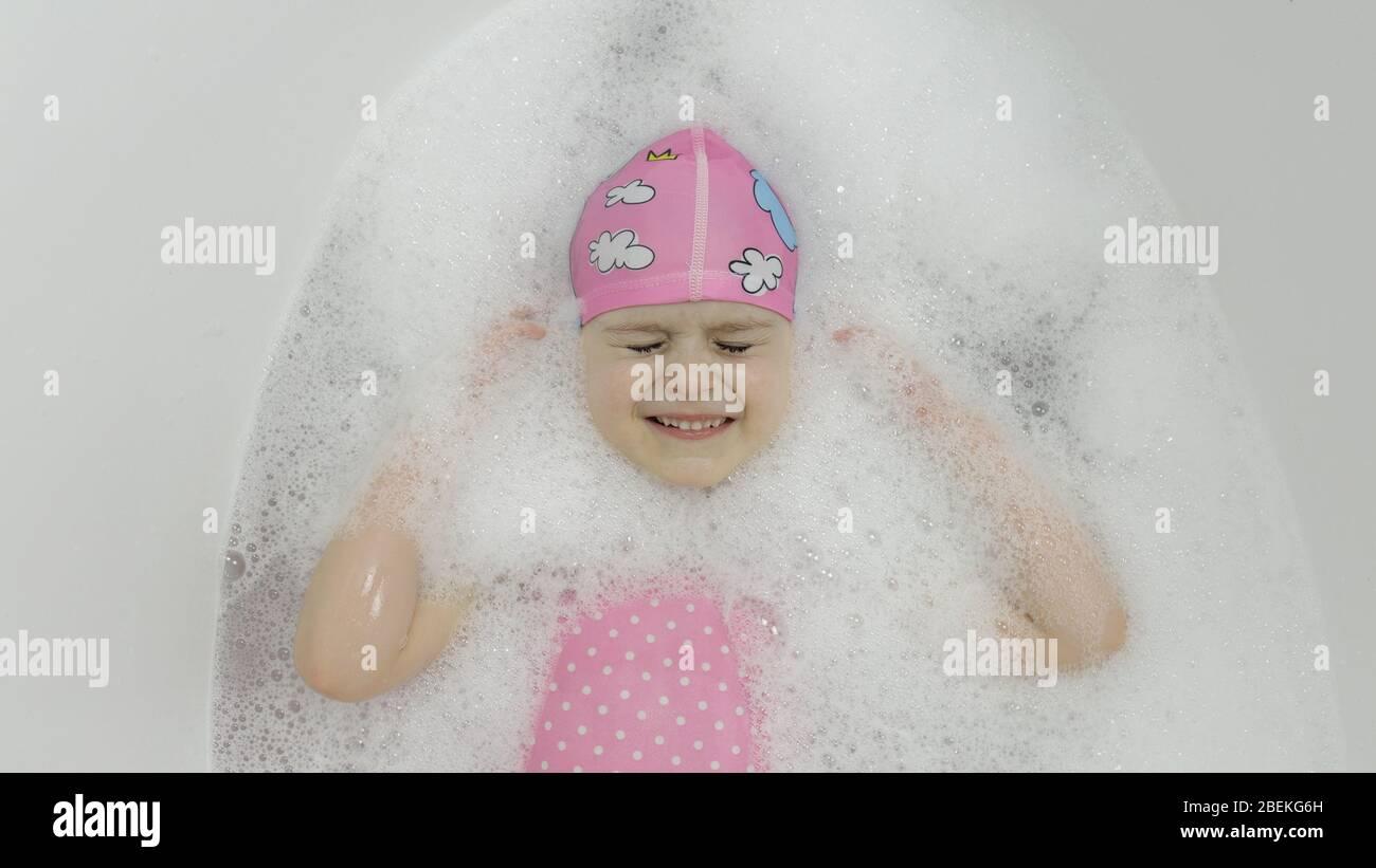 Attraente ragazza di quattro anni prende un bagno con schiuma bagno in swimwear rosa e cuffia da bagno. Sdraiati nel bagno. Igiene per il bambino biondo carino. Ragazza carina sorridente. Piccola bambina bionda in bagno Foto Stock
