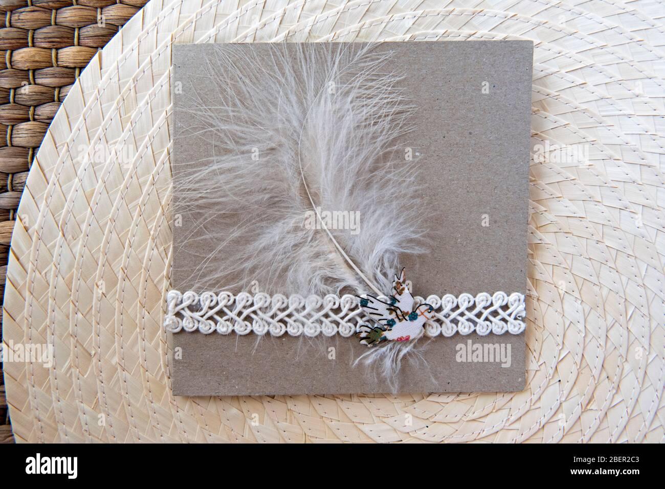 Carta fatta a mano con piuma riciclata, rifinitura e broccia su sfondo foglia di palma. Concetto di zero sprechi. Foto Stock