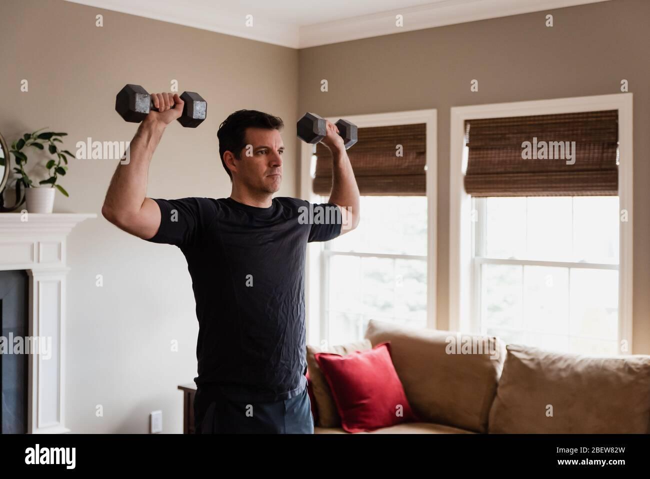 Uomo in forma che esercita a casa con pesi delle mani nel suo soggiorno. Foto Stock