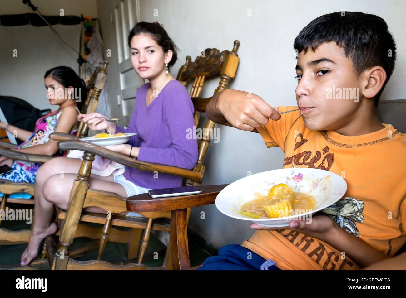 Scena reale di una famiglia latina che condivide il pranzo, stanno avendo un pasto tradizionale fatto di mais. Foto Stock