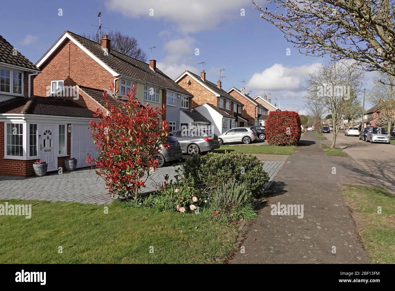 Case strada scena alcune case semi-distaccate pavimentazione sul giardino anteriore con vialetto pavimentato per parcheggio auto spazio alcuni mantenere casa prato Essex Inghilterra Regno Unito Foto Stock