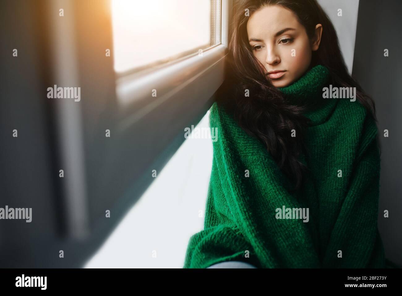 giovane donna infelice è triste vicino alla finestra. La brunetta piange. Tristezza, apatia, depressione e melancolia. Foto Stock