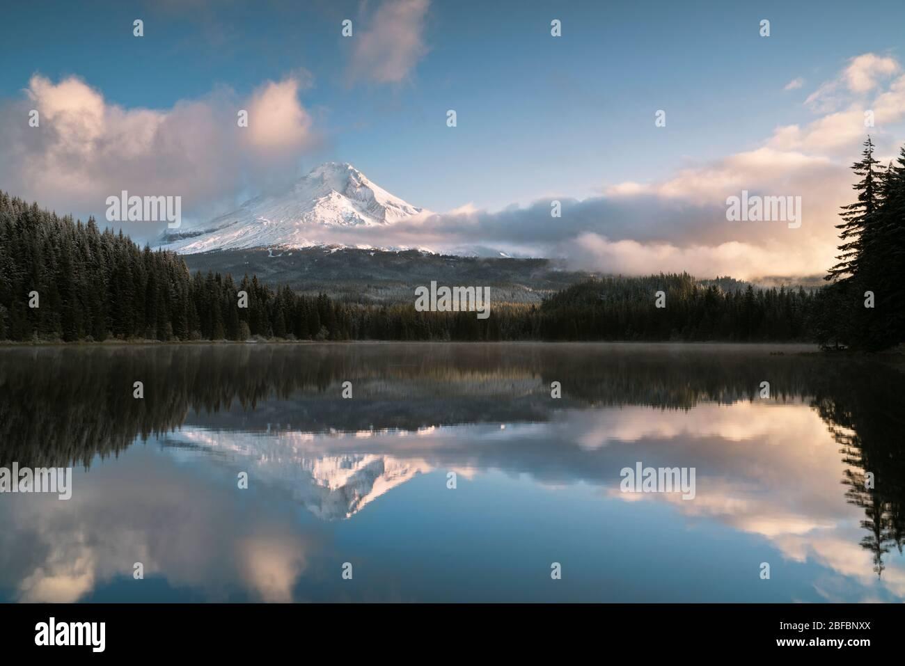 Le nuvole si rompono al mattino presto rivelando una fresca nevicata autunnale sul monte Hood dell'Oregon che si riflette nel lago Trillium. Foto Stock