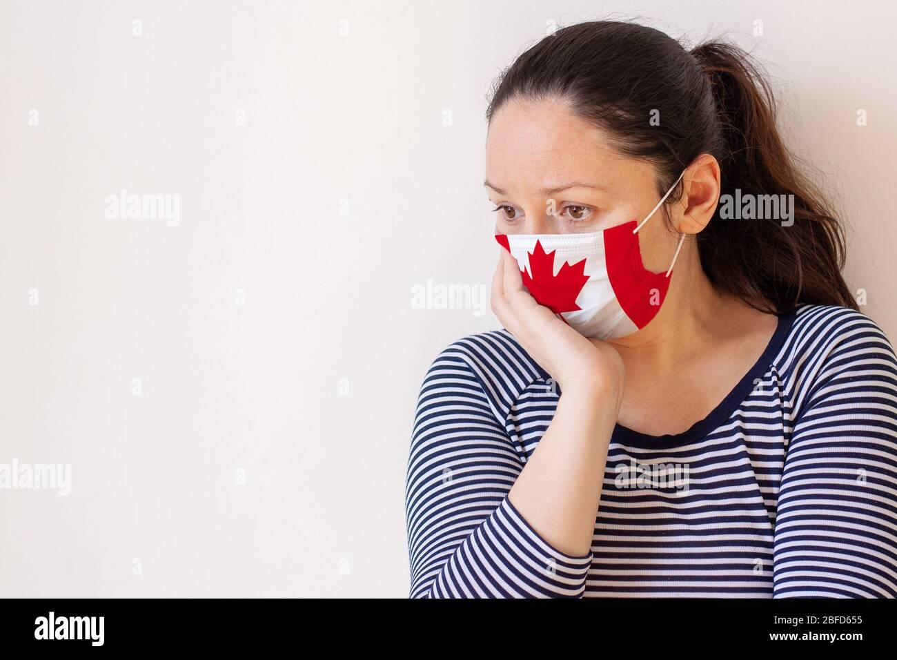 Una ragazza in un maglione a righe e maschera medica dipinta come la bandiera del Canada con attenzione la testa con la sua mano e guarda verso lo spazio delle copie Foto Stock