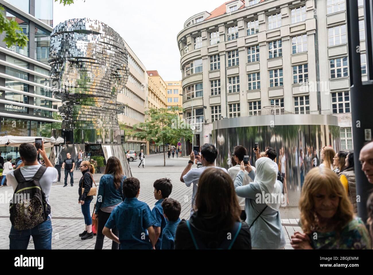 Persone, turisti che guardano la testa di Franz Kafka conosciuta come la statua di Kafka scultura all'aperto di David Cerny, installato fuori del Quadrio shopping Foto Stock