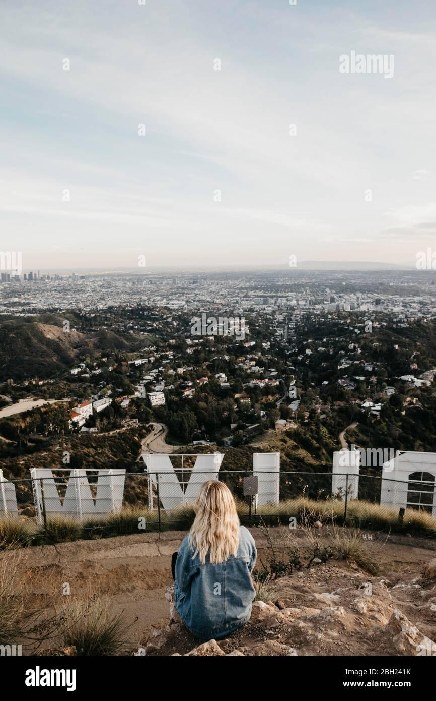 Vista posteriore della donna bionda seduta dietro l'insegna di Hollywood guardando la vista, Beverly Hills, USA Foto Stock