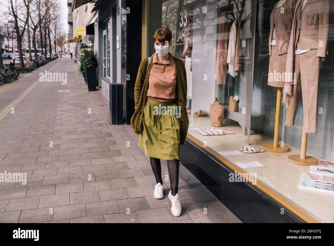 Donna che indossa una maschera che cammina lungo il negozio di abbigliamento in città Foto Stock