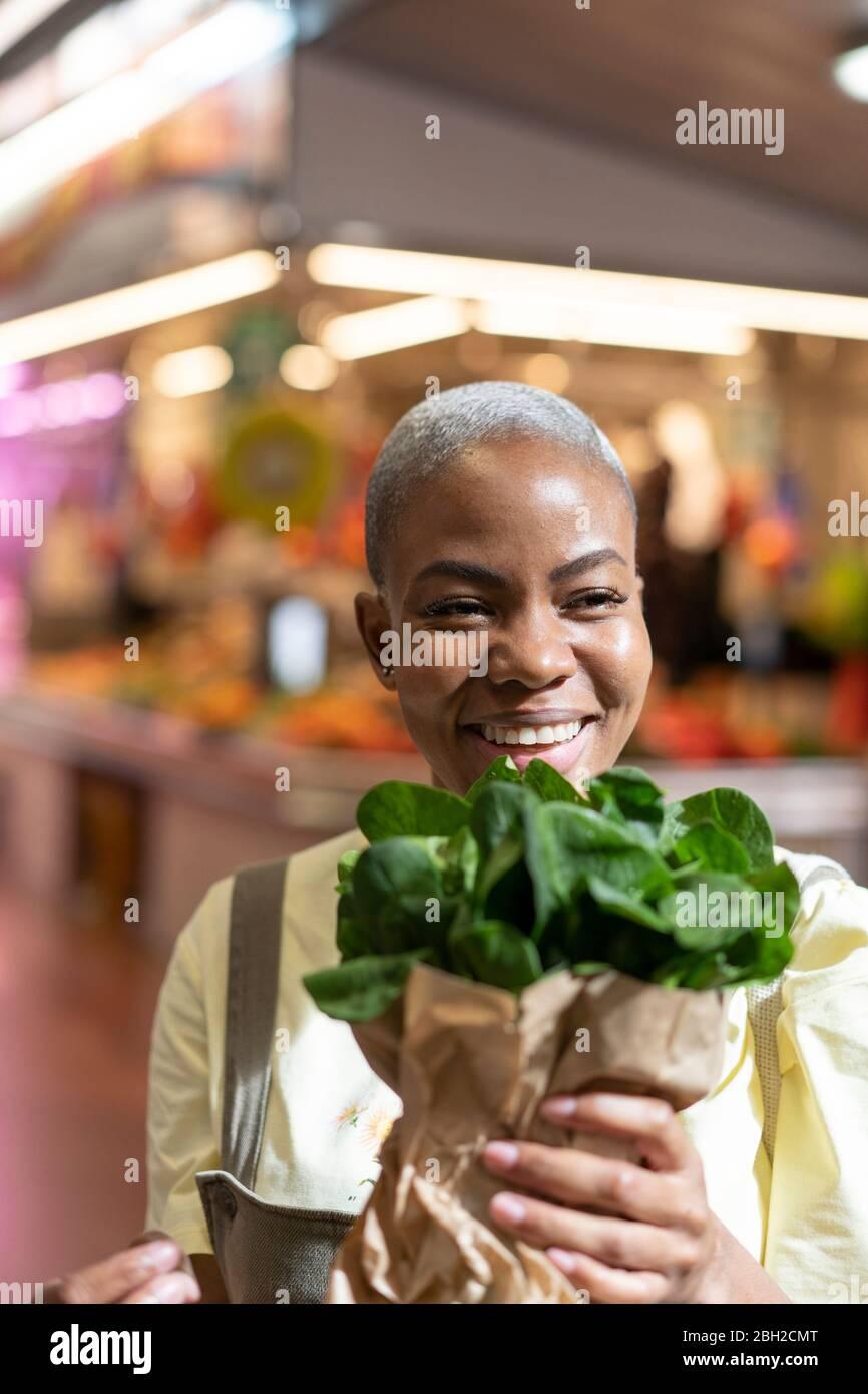 Ritratto di donna felice che tiene la borsa di carta in una sala mercato Foto Stock