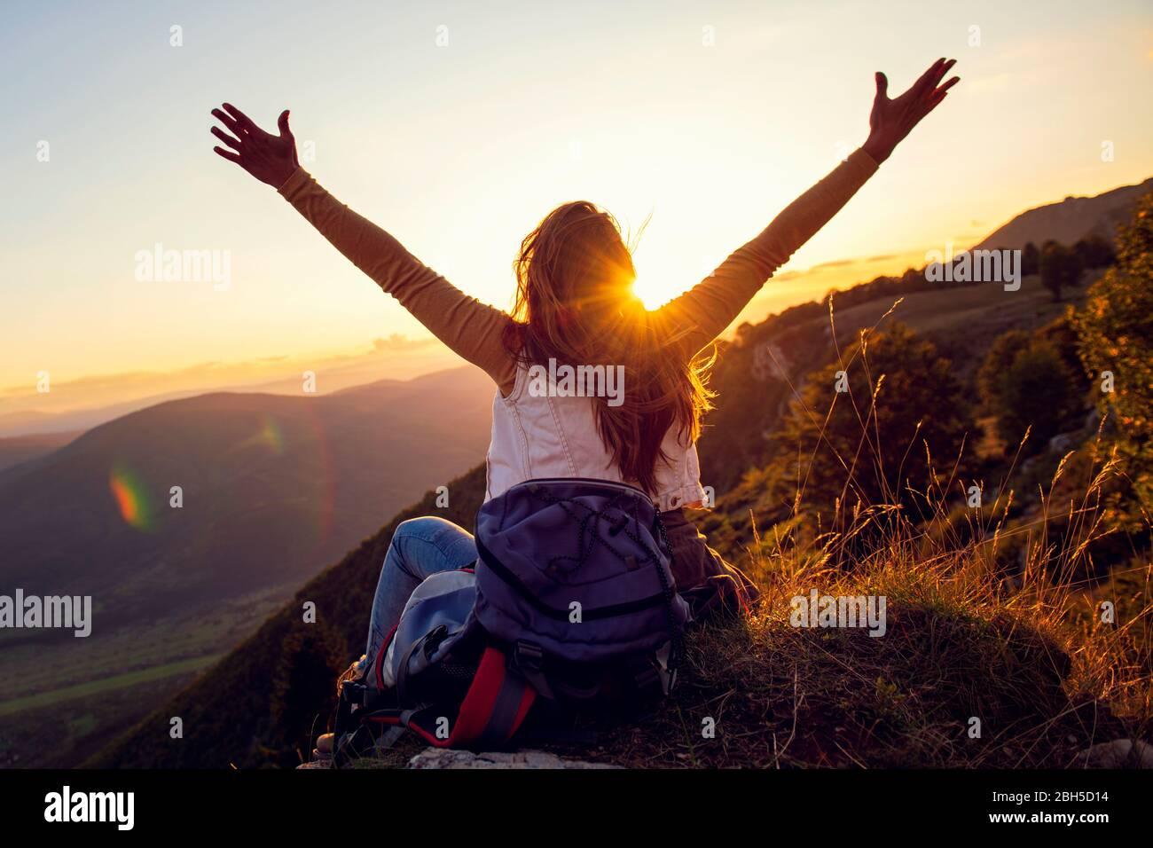 Giovane donna alzarsi mano su in cima alla montagna e tramonto cielo sfondo astratto. Foto Stock