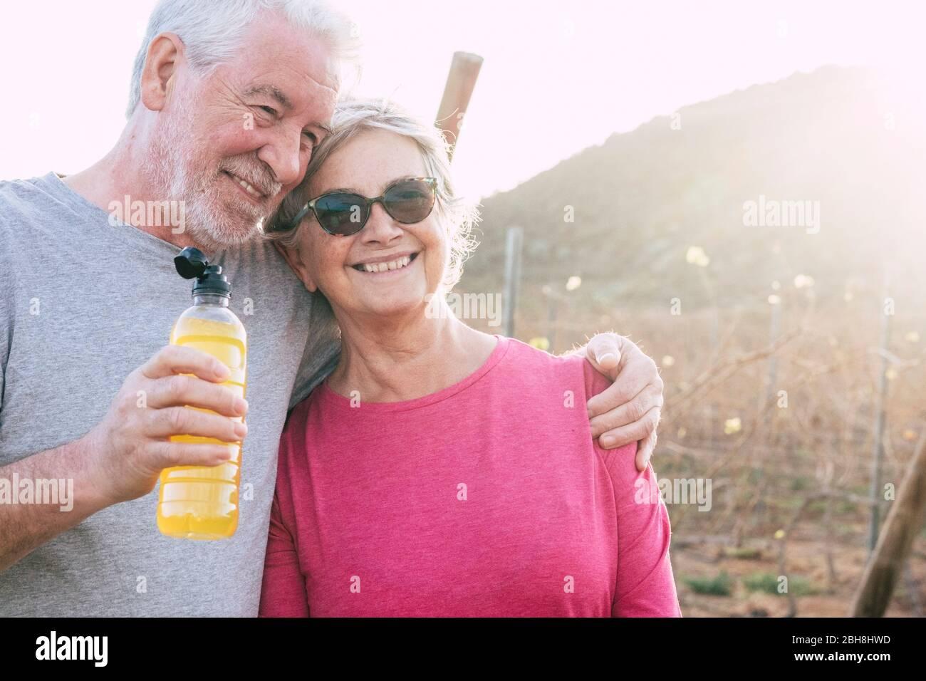 Felice allegro anziano sorriso di coppia e godere insieme per sempre la vita in campagna all'aperto lato con il sole in retroilluminazione dopo una sessione di fitness sana Foto Stock