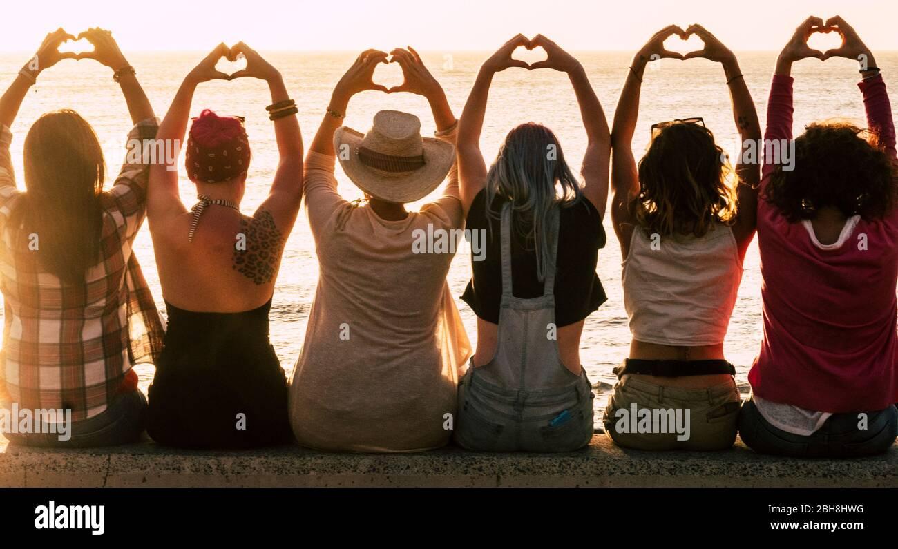 Concetto di stile di vita di amore e meditazione - gruppo di donne che guardano il tramonto sull'oceano e fanno il cuore con le mani - romantica luce dorata e concetto di giorno di San Valentino - amishp per sempre Foto Stock
