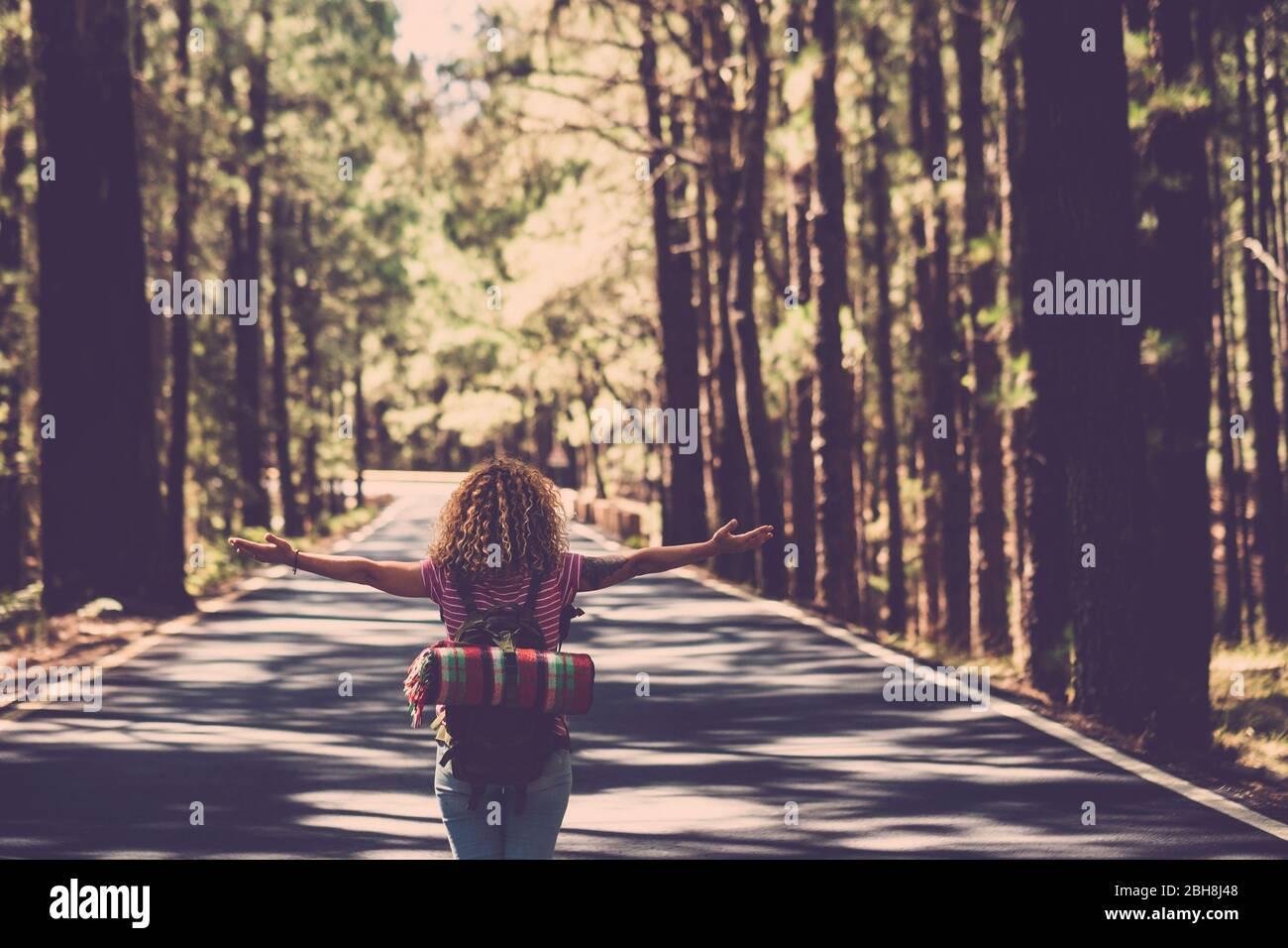 Eternità e successo soddisfazione vita concetto con la ragazza solitaria riccio hai rin il mezzo della strada lunga nella foresta con braccia aperte e zaino - wanderlust e viaggi stile persone Foto Stock