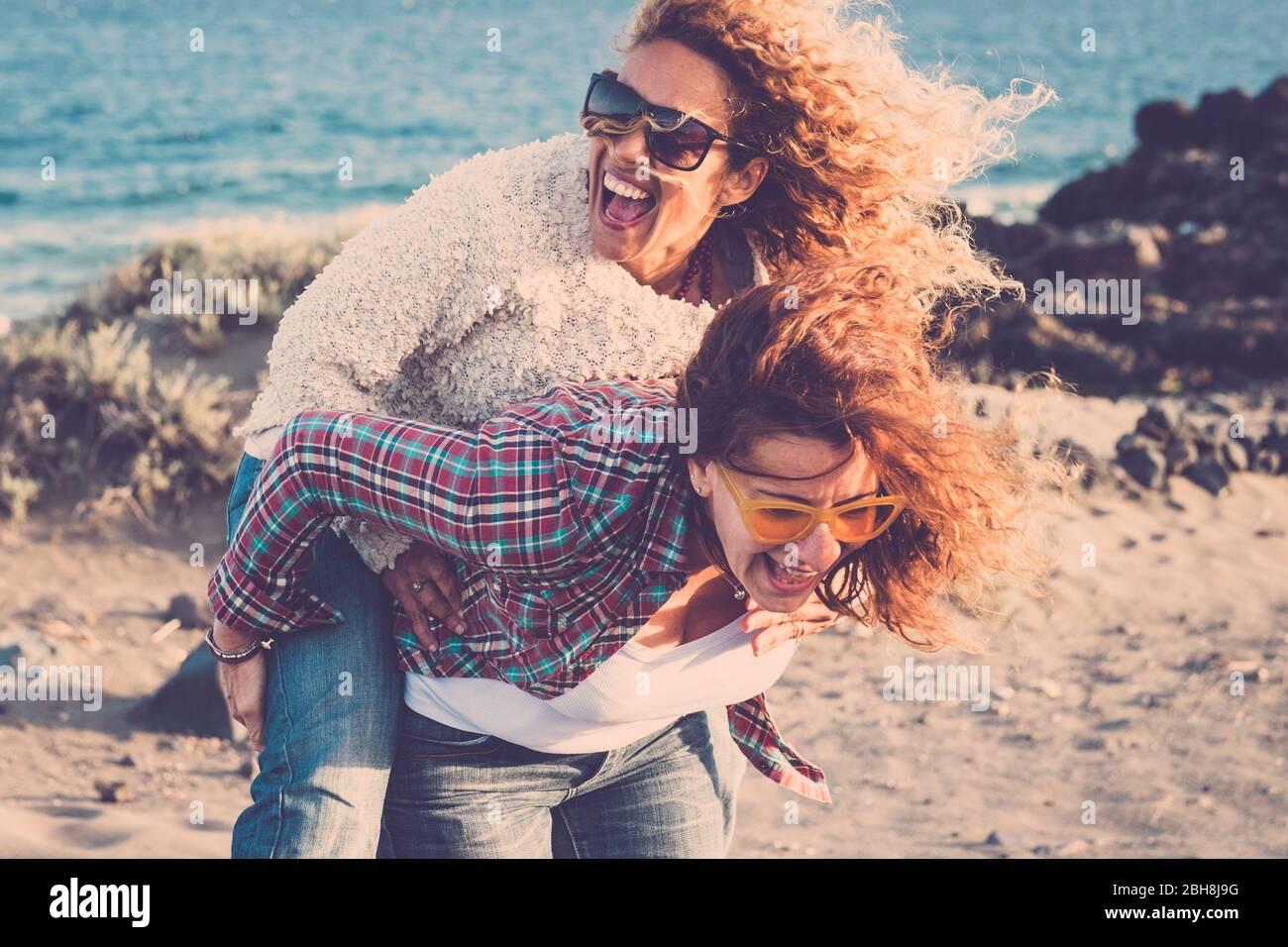 La gente ride molto e si diverte insieme in amicizia in attività di svago all'aperto - coppia di donne sono andati pazzo portando eachother sulla spalla - nessun limite di età per essere giocoso e felice Foto Stock