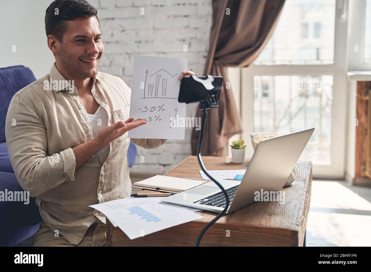 Blogger seduto di fronte alla fotocamera del cellulare Foto Stock