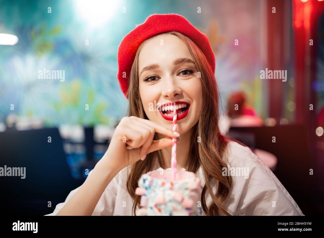 Ragazza con denti bianchi, bel sorriso in berretto rosso, Francia bevande rosa fragola milkshake dalla paglia Foto Stock