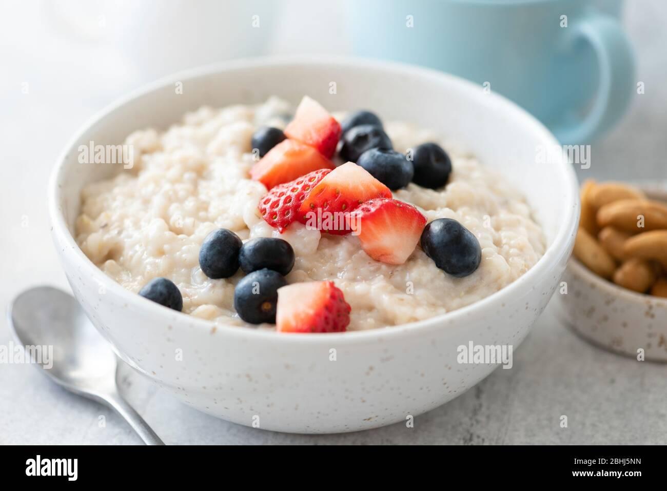 Prima colazione porridge farinata d'avena con fragola, mirtillo in ciotola bianca, vista Closeup di pasto sano prima colazione Foto Stock