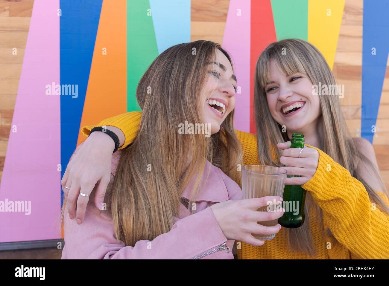 Due giovani donne caucasiche felici brindano con un drink sulla parete multicolore di un bar della città Foto Stock