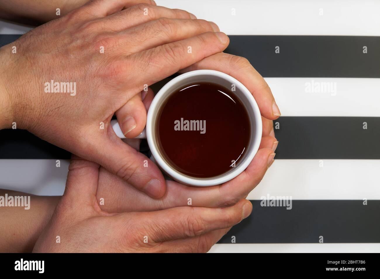 Coppia amorevole sul rapporto, affettuosamente tenendo le mani sopra la tazza della bevanda vista superiore.maschio teneramente che tocca le mani femminili che tengono una tazza del tè a casa Foto Stock