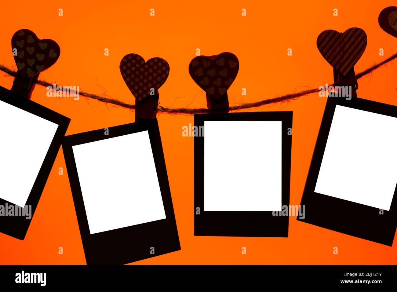 cinque clip di carta di clothespins rossi con un cuore su una corda. San Valentino amore. Lava sfondo lussureggiante. Spazio copia. Mocap Foto Stock