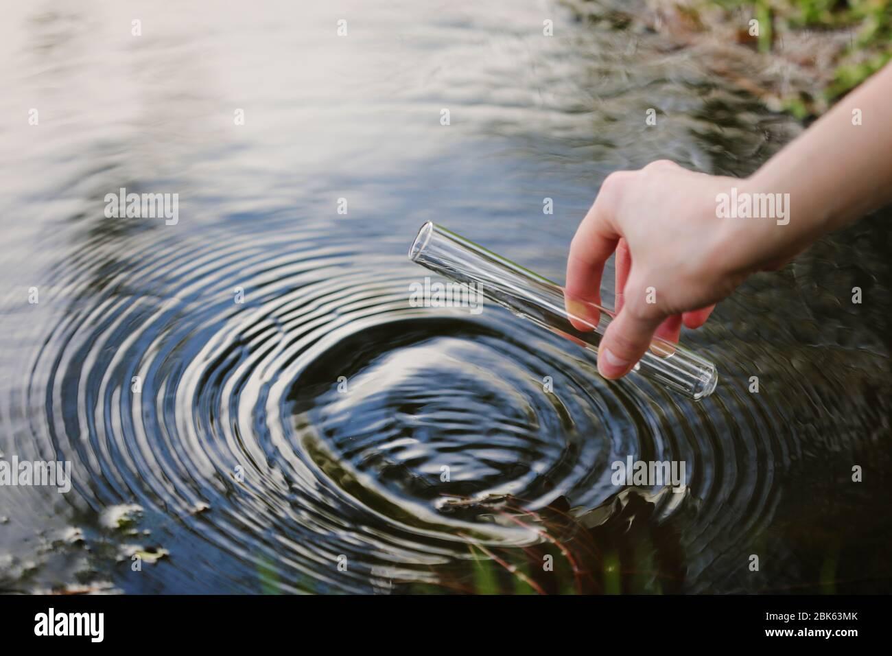 Campione di acqua. La mano raccoglie l'acqua da esplorare. Concetto - analisi della purezza dell'acqua, ambiente, ecologia. Analisi dell'acqua per le infezioni, permesso di nuotare Foto Stock